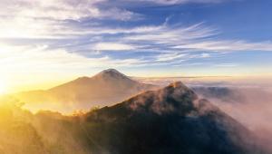 Wulkan BaturWulkan Batur, choć wciąż aktywny, dostępny jest dla wszystkich. Wznosi się zaledwie na wysokość 1,700 metrów ponad poziom morza, ale widok z jego szczytu jest naprawdę spektakularny – zwłaszcza podczas wschodu słońca, kiedy to wspaniały krajobraz powoli wyłania się z ciemności.Jeżeli chcemy tego doświadczyć, trzeba wyruszyć około trzeciej nad ranem. Trasa z wioski Toya Bungkah, leżącej na skraju jeziora u stóp wulkanu, zajmuje około dwóch godzin. Pokonanie jej nie jest męczące, jedyne o czym trzeba pamiętać to zakryte obuwie, ponieważ na ścieżce zdarzają się kamienie. Na wierzchołek należy dotrzeć około piątej, ale już wcześniej czeka Was wiele niezapomnianych przeżyć. Jeszcze zanim słońce zacznie wyłaniać się zza horyzontu, cała okolica budzi się wyczuwając nadchodzący dzień. Narastające odgłosy podekscytowanych zwierząt, dźwięki odbijające się od krateru wulkanu, to przeżycie tak emocjonujące, że zanim się obejrzycie będziecie już na szczycie wulkanu. Wystarczy jeszcze tylko chwilę poczekać na świt. Pierwsza łuna słonecznego światła wynurza się zza góry Agung. Promienie stopniowo odsłaniają kolejne szczyty leżące po przeciwległej stronie jeziora Danau Batur. Widzimy jak światło odbija się od jego tafli, w końcu pada także na obręcz krateru na którym stoimy, odsłaniając olbrzymie wulkaniczne stoki pokryte popiołem. Gdzieniegdzie widać nawet parę unoszącą się nad aktywnymi pęknięciami. Ten widok uświadamia nam, że rzeczywiście stoimy na wulkanie, na najaktywniejszym sejsmicznie obszarze na całym Bali! To najlepszy świetlny show, jaki kiedykolwiek przyszło nam oglądać. Z pewnością trudno o lepszą śniadaniową scenerię, dlatego bardzo często zwieńczeniem wyprawy jest wspólne śniadanie – jajka na twardo gotowane bezpośrednio nad parą wydobywającą się ze skalnych szczelin.
