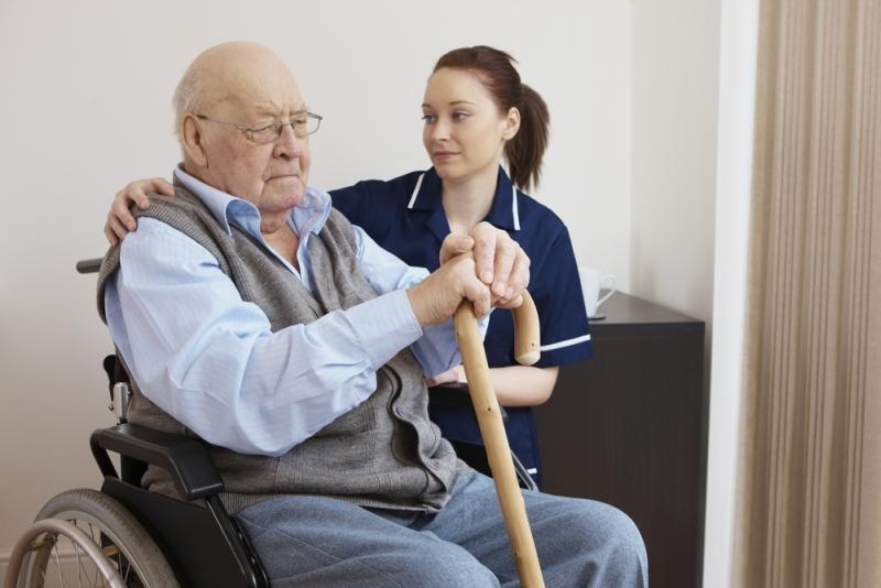 Mężczyzna na wózku inwalidzkim rozmawia z pielęgniarką. fot. shutterstock.com